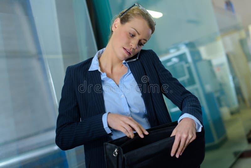 看在袋子的女实业家,当接打电话时 库存图片