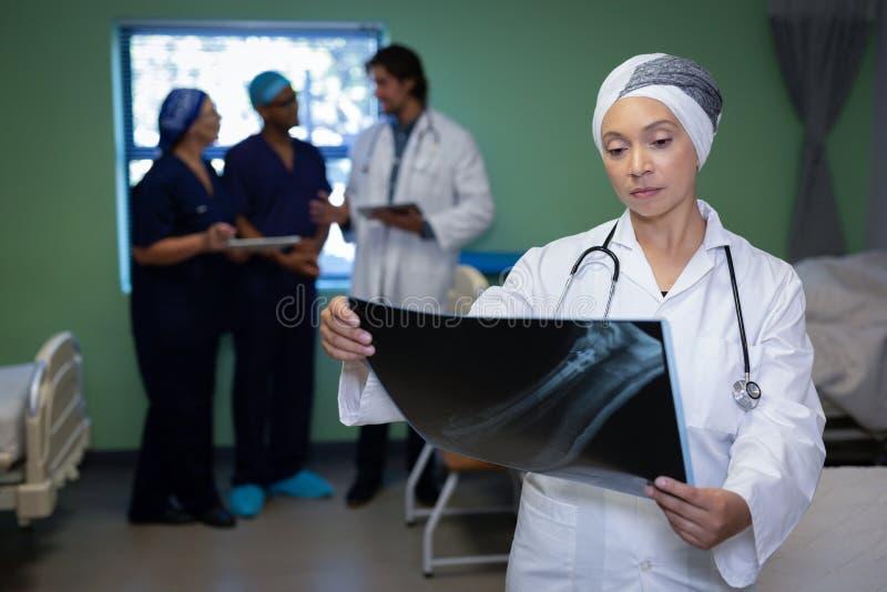 看在诊所的成熟的女性医生X-射线报告医院 库存照片