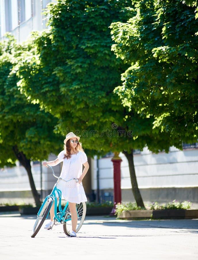 看在距离的白色礼服的美丽的女性骑自行车的人,当在市中心时骑她的蓝色自行车 库存照片