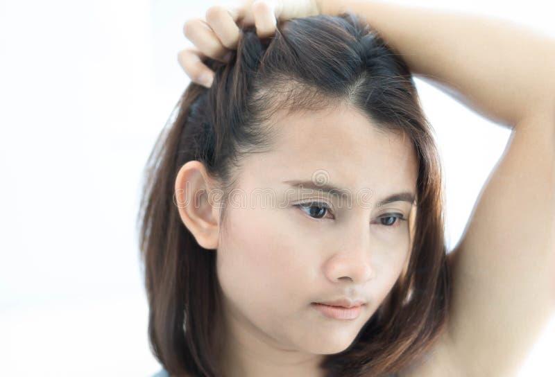 看在镜子严肃的掉头发问题的妇女反射为医疗保健香波和美容品概念 免版税库存照片