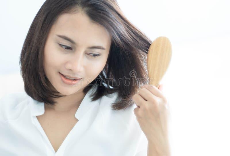 看在镜子严肃的掉头发问题的妇女反射为医疗保健香波和美容品概念 图库摄影