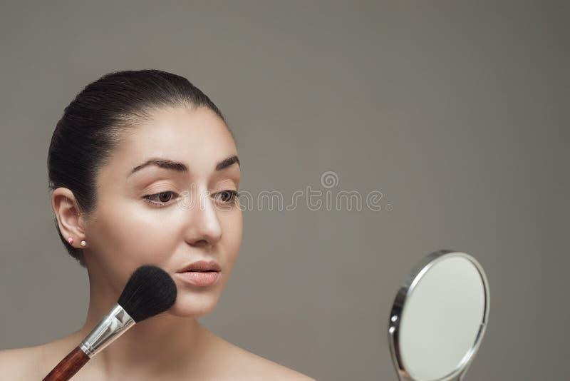 看在镜子和应用与一把大刷子的美丽的女孩化妆用品 库存照片