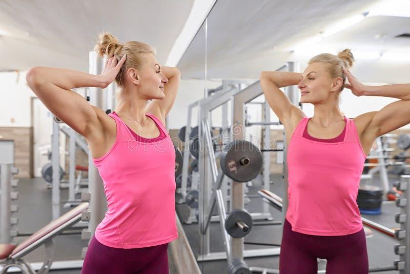 看在镜子的健身房的年轻美丽的运动妇女金发碧眼的女人 人秀丽健身体育健康生活方式概念 免版税库存照片