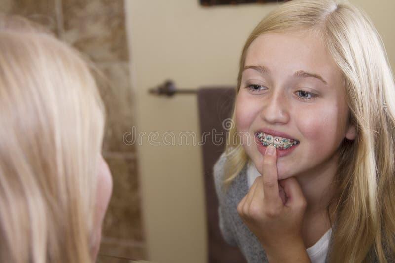 看在镜子的女孩,审查她括号 免版税库存照片