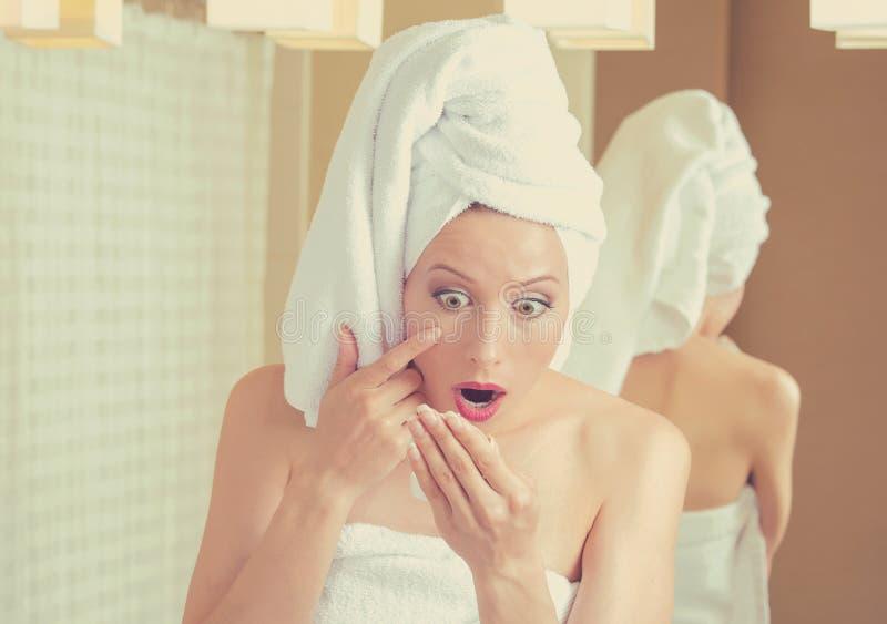 看在镜子的惊奇的妇女怏怏不乐对于在面孔的皱痕 库存照片