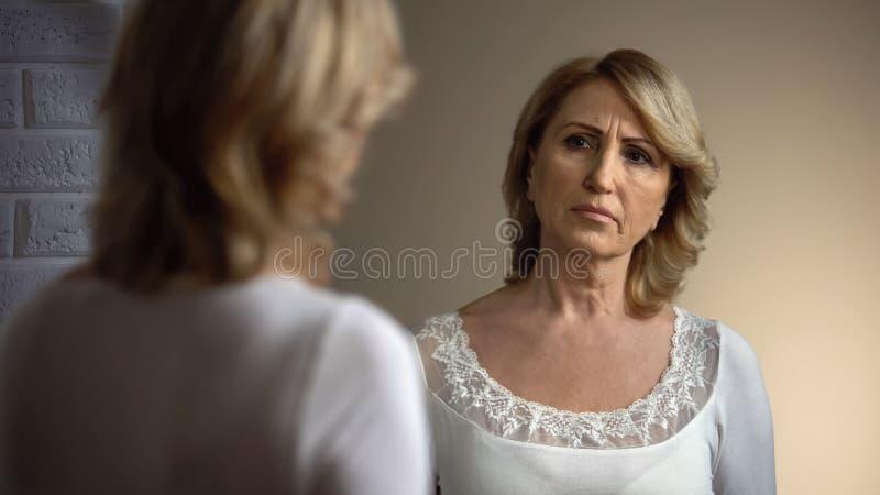 看在镜子的白色礼服的沮丧的老妇人反射,问题 免版税库存照片