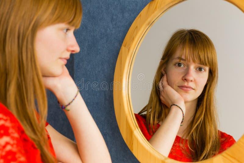 看在镜子的红头发人十几岁的女孩 库存照片