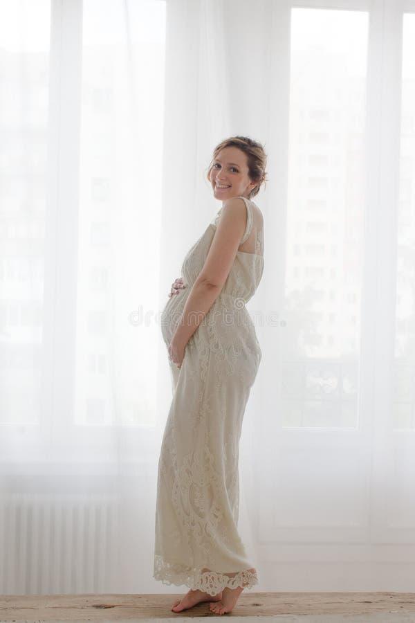 看在长凳的典雅的孕妇照相机 库存图片