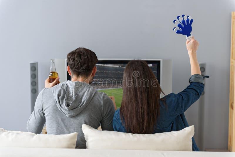 看在长沙发的男人和妇女电视 免版税库存图片
