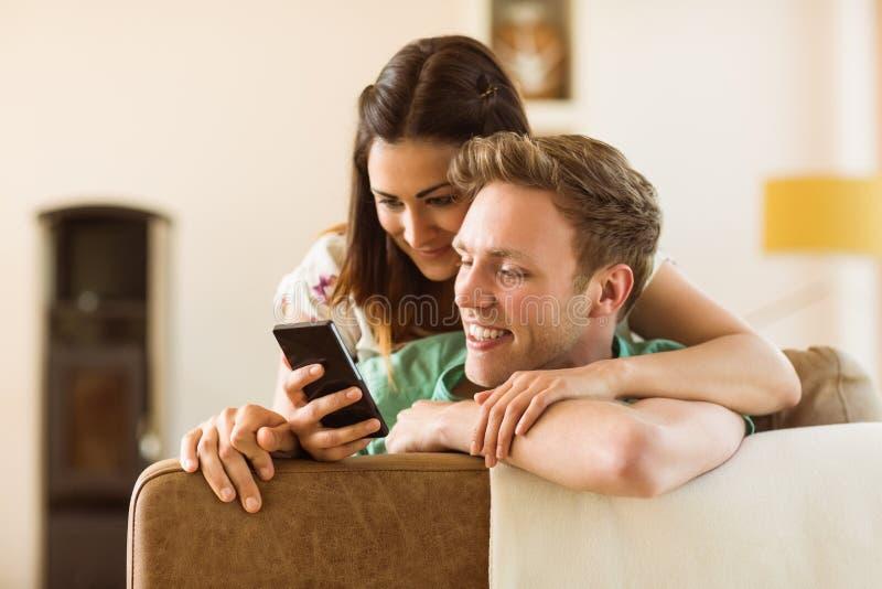 看在长沙发的逗人喜爱的夫妇智能手机 免版税库存图片
