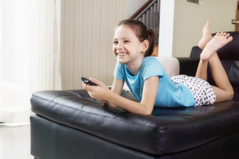 看在长沙发的逗人喜爱的青春期前的女孩电视使用遥控 客厅内部在背景中 免版税库存图片