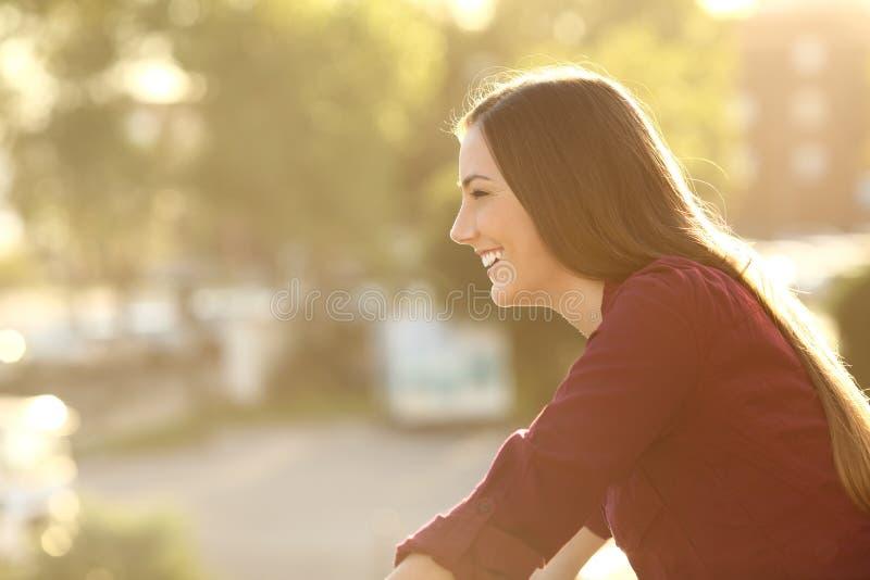 看在阳台的愉快的妇女 库存照片