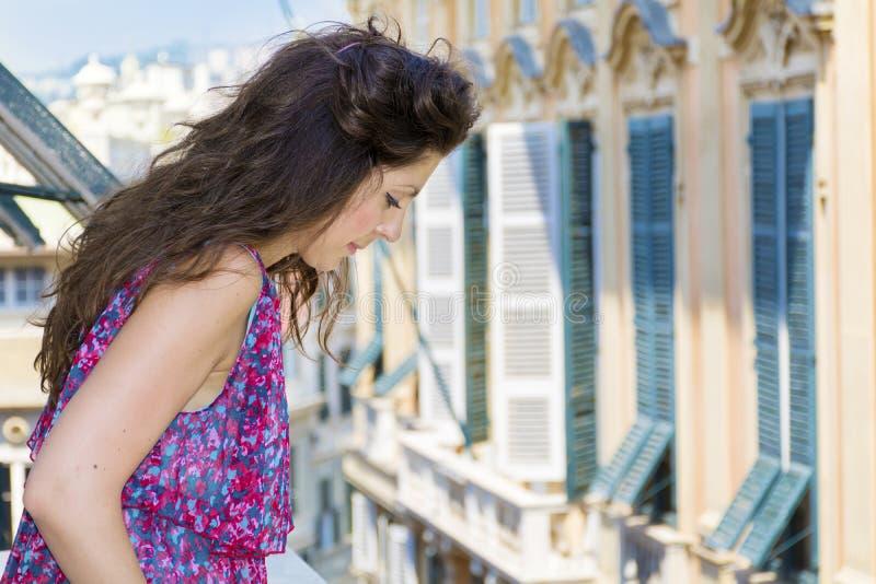 看在阳台的年轻美丽的妇女在市赫诺瓦,意大利 免版税图库摄影