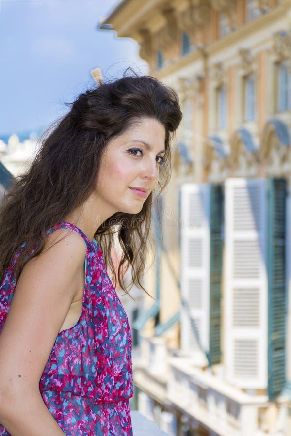 看在阳台的年轻美丽的妇女在市赫诺瓦,意大利 库存图片