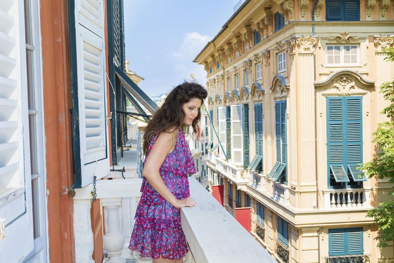看在阳台的年轻美丽的妇女在市赫诺瓦,意大利 免版税库存照片