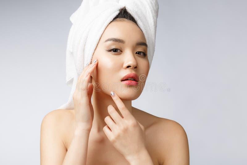 看在面孔的亚裔妇女丘疹 年轻女人设法去除她的丘疹 亚洲背景美好的秀丽关心白种人概念女性查出混合模型纵向种族皮肤白人妇女 查出在白色 免版税库存图片