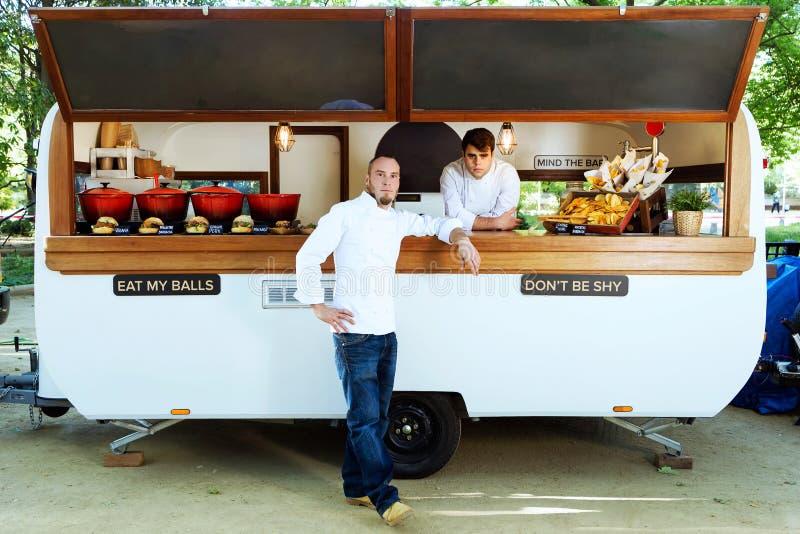 看在食物卡车的英俊的年轻厨师照相机 免版税库存图片