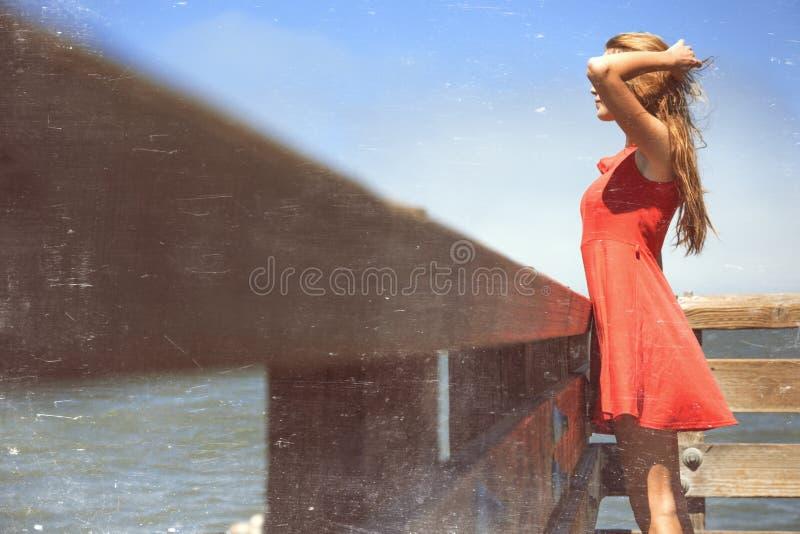 看在水上的sundress的青少年的女孩 免版税库存图片