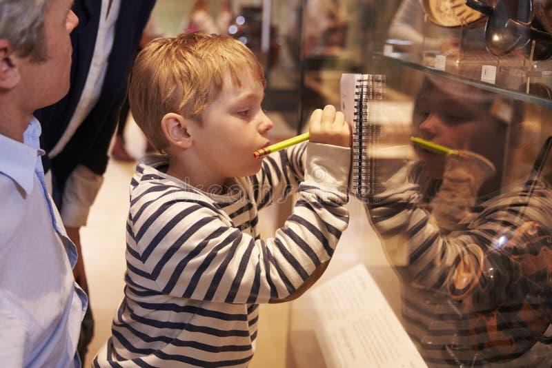 看在玻璃容器的家庭人工制品在旅行对博物馆 免版税库存图片