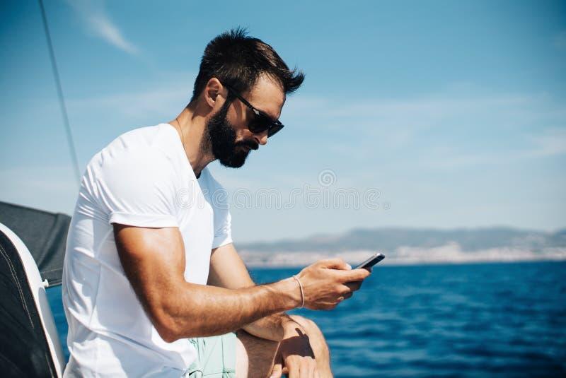 看在他的智能手机的有胡子的人照片  免版税库存照片