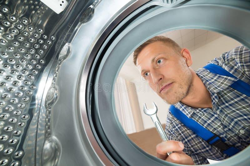 看在洗衣机里面的安装工 库存照片