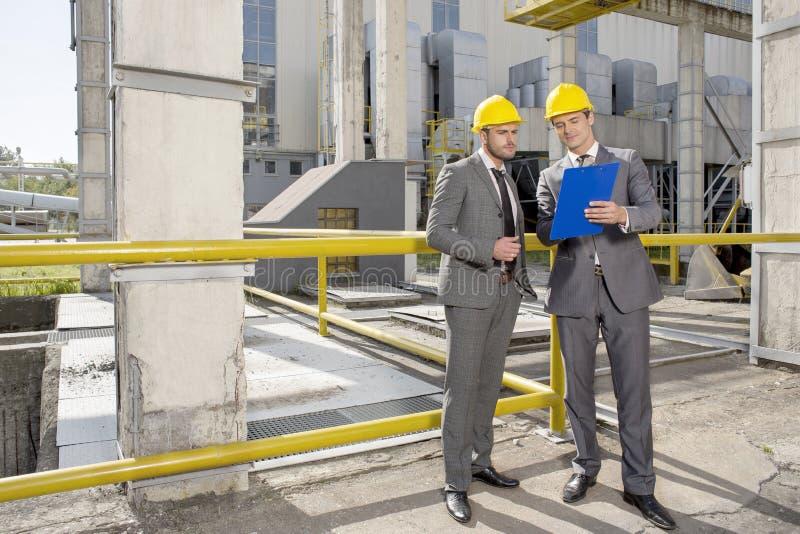 看在建造场所的全长年轻男性建筑师剪贴板 免版税库存图片