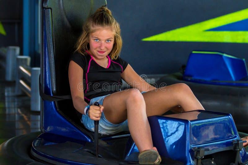 看在a的碰撞用汽车乘驾的厚脸皮的女孩照相机 免版税库存图片