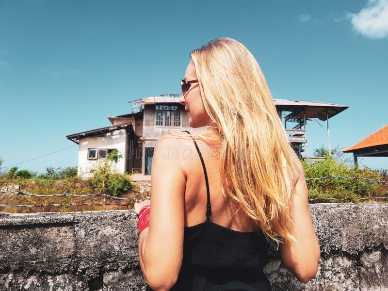 看在barbwire篱芭后的妇女被放弃的大厦 免版税库存图片
