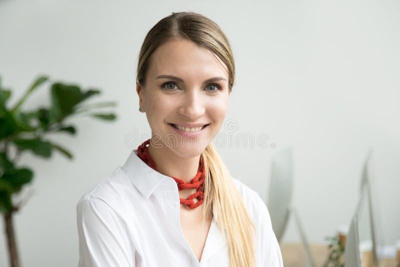 看在offic的可爱的微笑的职业妇女照相机 免版税库存图片