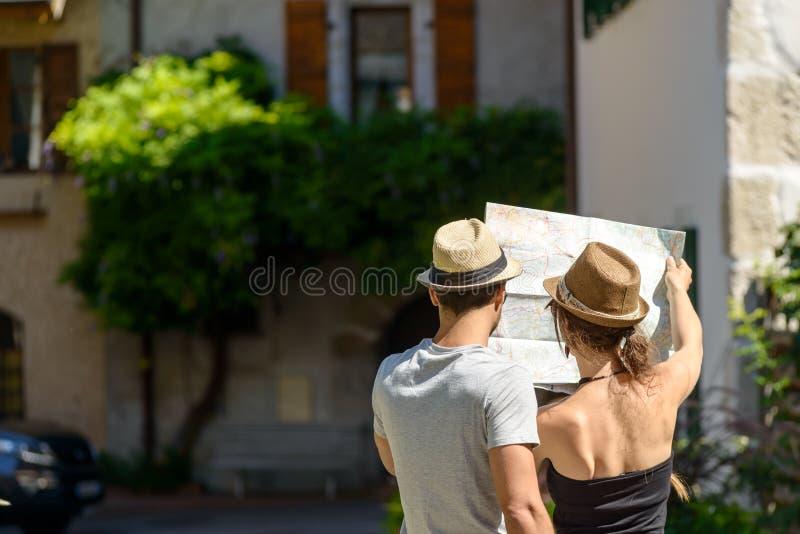 看地图的一对年轻夫妇, 库存照片