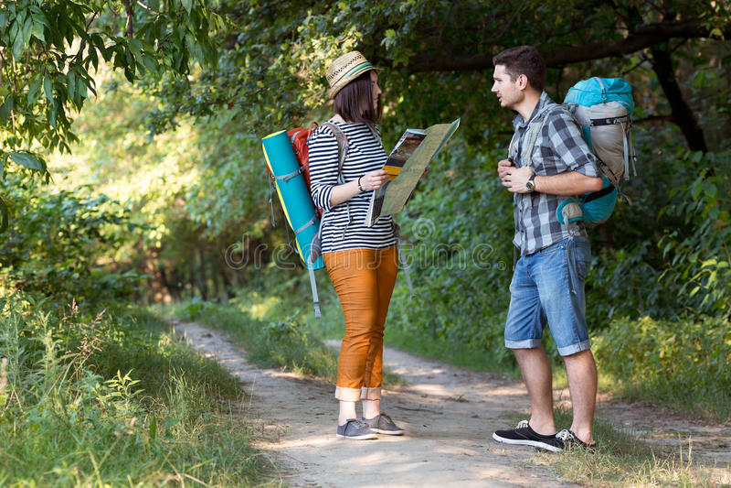看地图的两个远足者停留在森林足迹 库存照片
