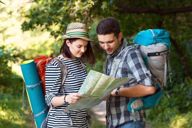 看地图的两个远足者停留在森林足迹 免版税库存图片