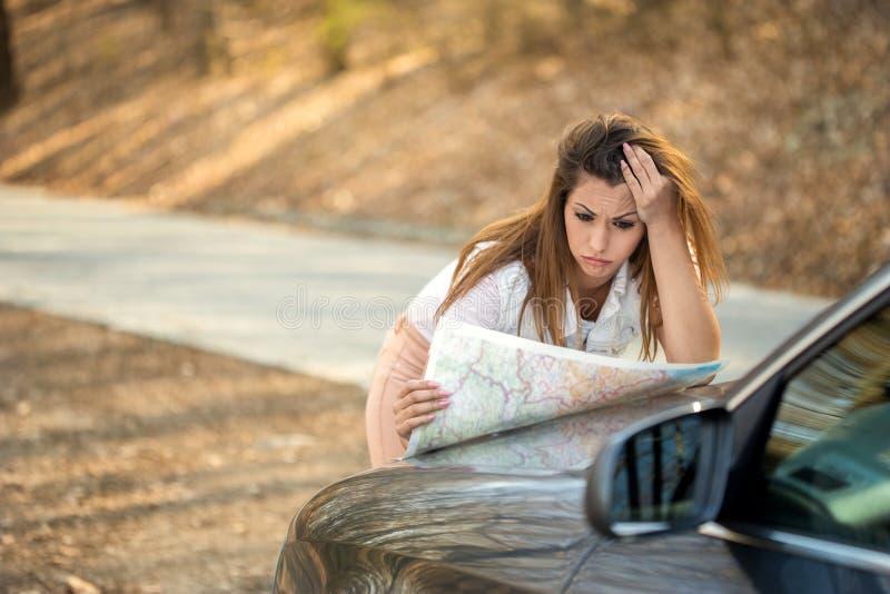 看地图的美丽的失去的妇女在路一边 图库摄影
