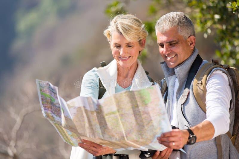 看地图的资深远足者 免版税库存照片