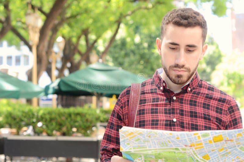 看地图的年轻旅游人 免版税库存照片