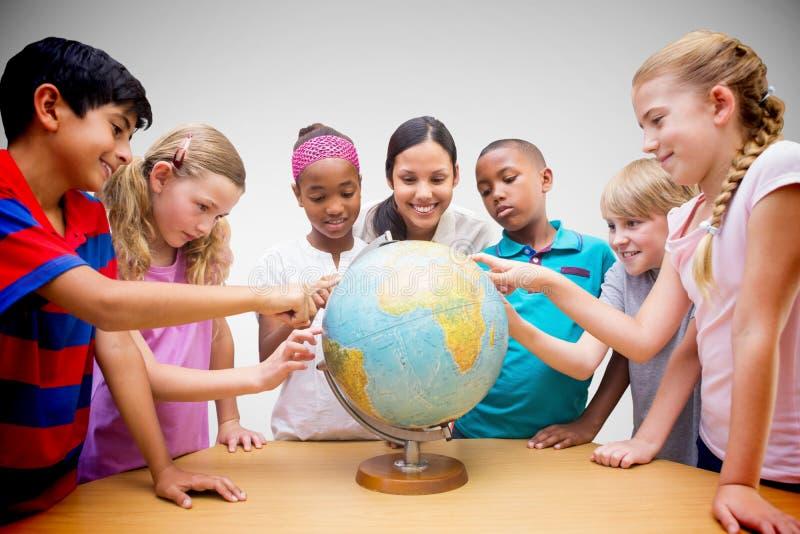 看地球的逗人喜爱的学生和老师的综合图象在图书馆里 库存照片