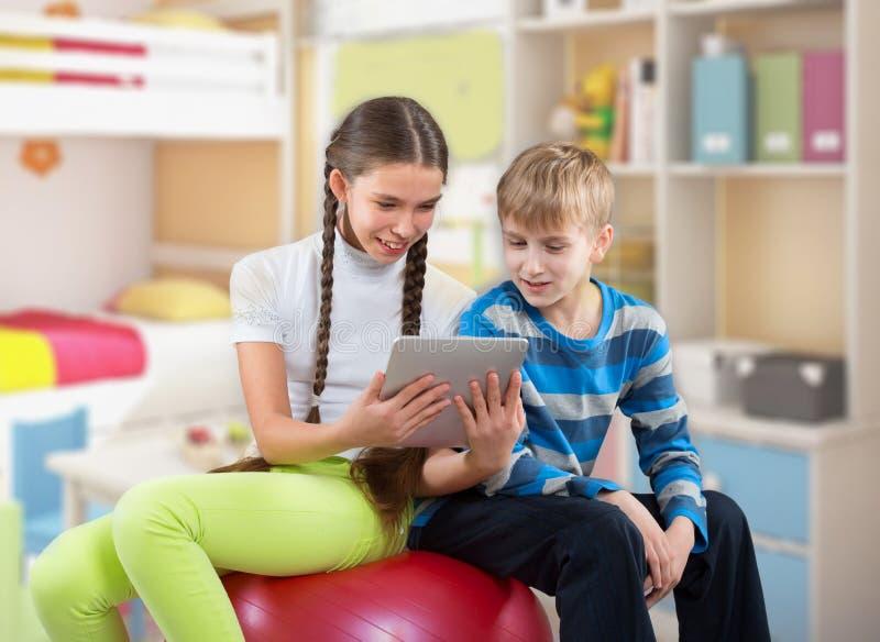 看垫的女孩和男孩压片个人计算机屏幕 免版税图库摄影