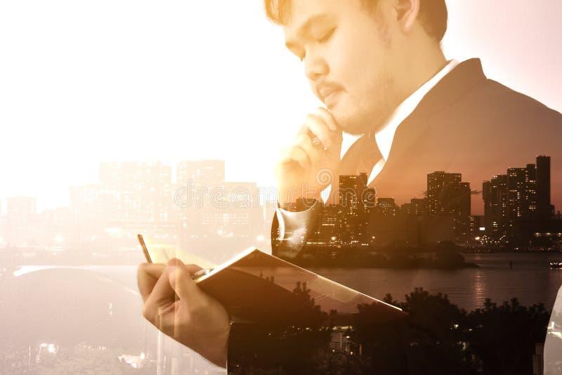 看备忘录和认为为想法,两次曝光,全景当代特大的城市背景,橙色太阳的商人 免版税库存图片