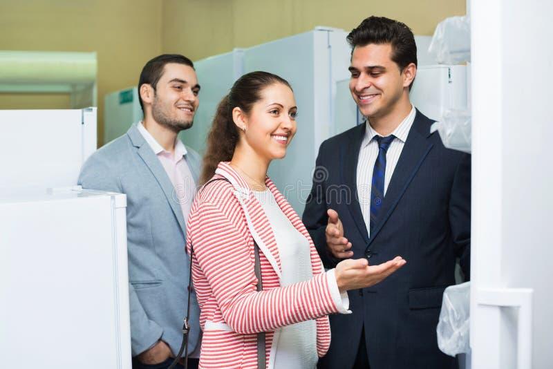 看大冰箱的微笑的美好的夫妇 免版税库存照片