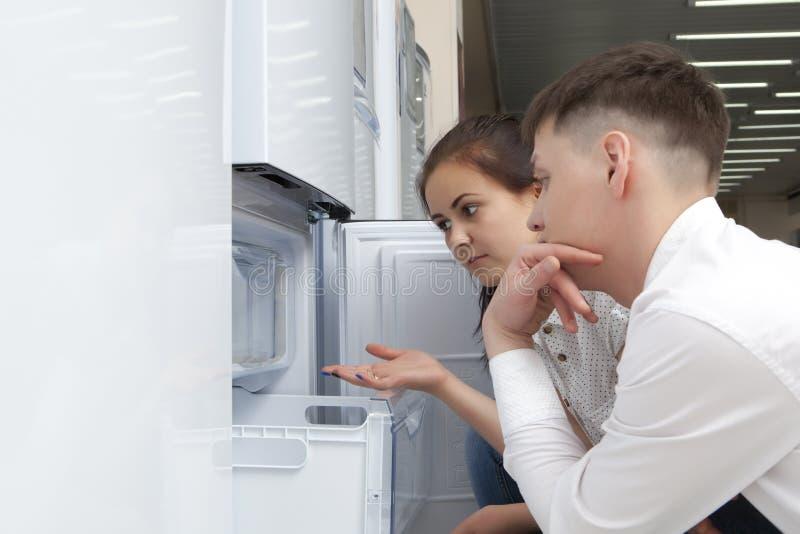 看大冰箱的愉快的家庭夫妇 免版税库存照片