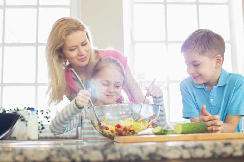 看女孩混合的沙拉的家庭在厨房里 免版税图库摄影