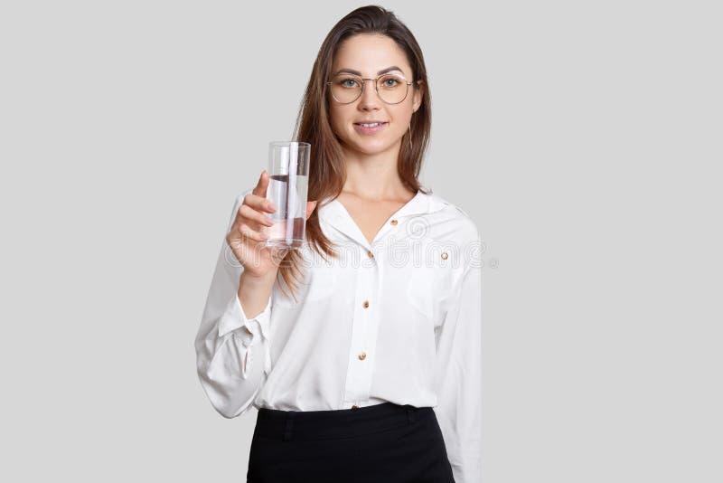 看女实业家的pleasnt室内射击穿白色女衬衫,光学玻璃,拿着杯水,看直接地入照相机 库存图片