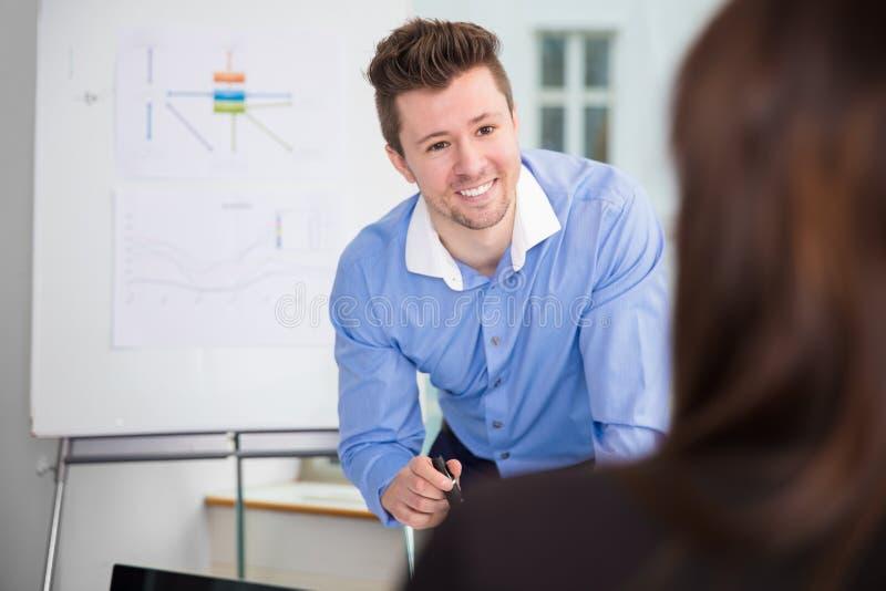 看女性同事的微笑的商人在办公室 库存照片