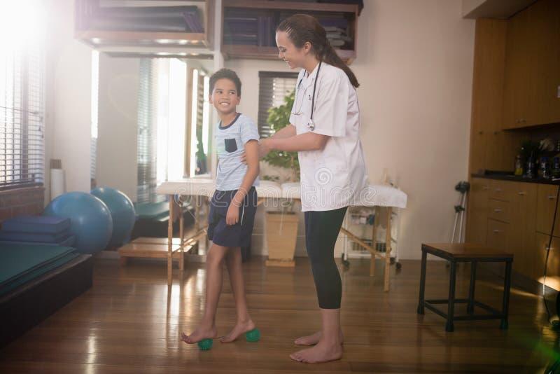 看女性治疗师的微笑的男孩侧视图,当站立在重音球时 库存图片