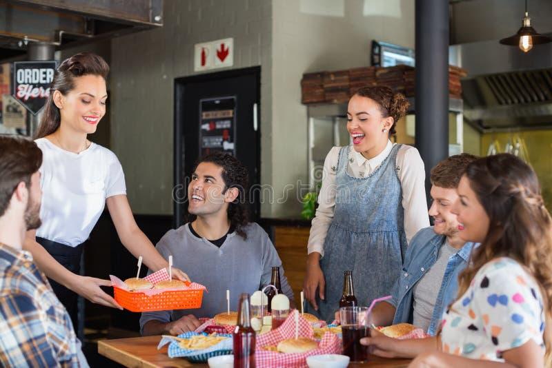 看女服务员服务食物的朋友在餐馆 免版税图库摄影