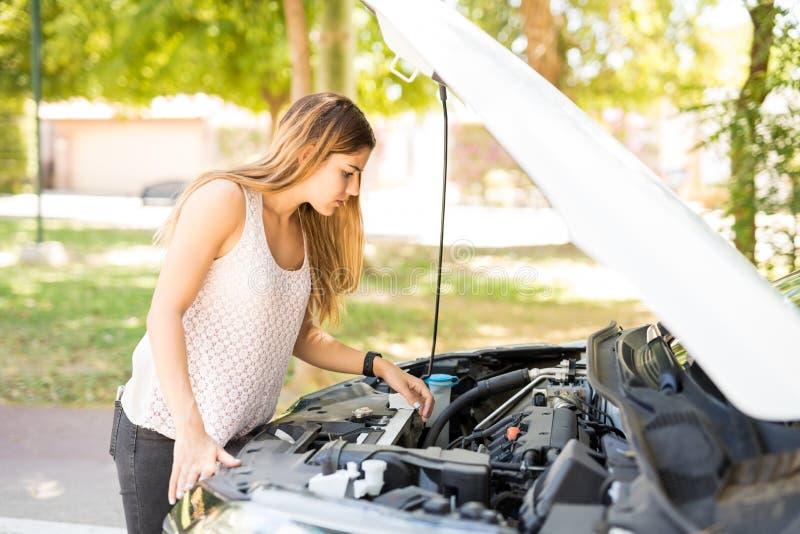 看她残破的汽车的引擎妇女 库存图片
