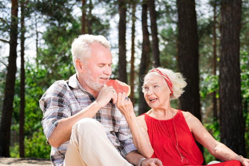 看她的丈夫的亲切的资深妇女,当给他的西瓜时 免版税库存图片