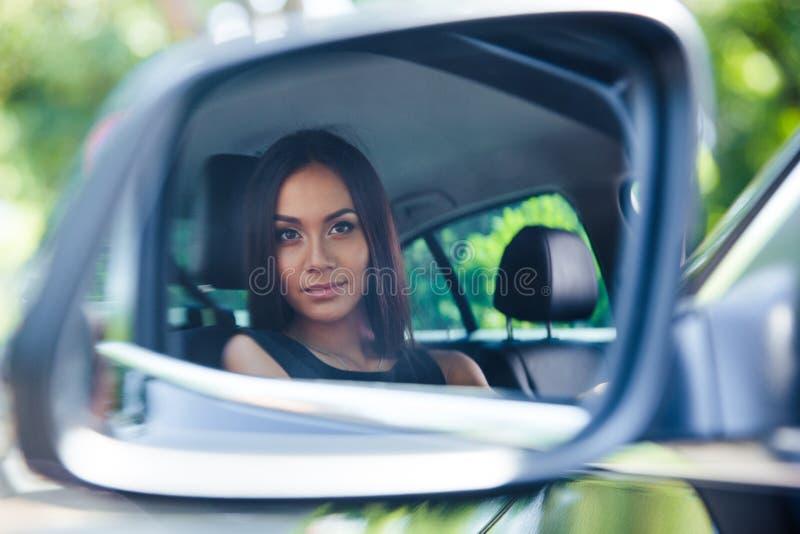 看她的在汽车镜子的妇女反射 免版税图库摄影