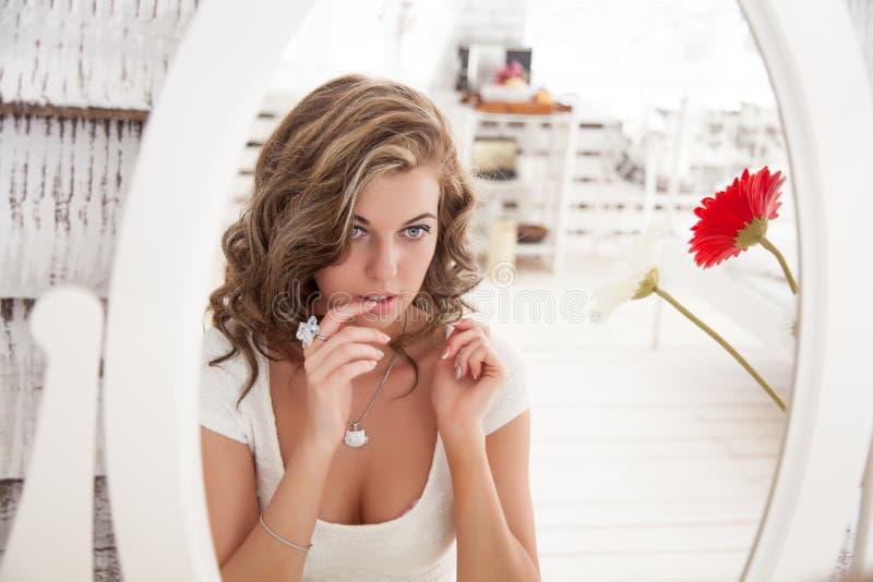 看她的在镜子的年轻美丽的妇女面孔 免版税库存图片