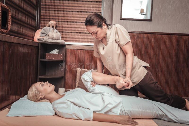 看她的客户腿的好严肃的妇女 免版税库存图片